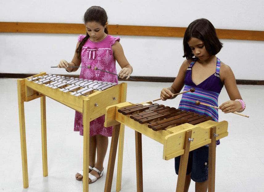 Meninas tocando metalofone e xilofone